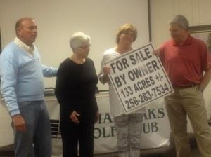 Donna Roberts (third from left) holds the For Sale sign for Indian Oaks Golf Club after he husband Lewis (left) announces his purchase of the facility.