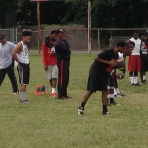 Anniston High football coach Eddie Bullock (C) knows the importance of getting things done in the summer.