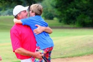Gary Wigington gets a celebratory hug from 11-year-old son Peyton after winning the Calhoun County Championship Sunday. In the main photo, Wigington is congratulated by his playing partners after finishing off his winning 66 with an eagle on 18. (All photos by Greg McWilliams.)