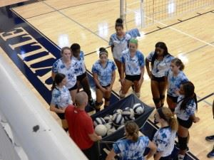 Jacksonville volleyball coach David Clark (red shirt) gathers his team during its final practice before opening the season Thursday night.