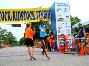 Marion Kandie is greeted after crossing the finish line as the woman's winner in Saturday's Woodstock 5K. In the cover photo, Patrick Cheptoek wins his third straight Woodstock. (Photos by Greg McWilliams) In the upper photo, Cheptoek wins his third straight Woodstock (Photo by Al Muskewitz) (Click on photos to enlarge)