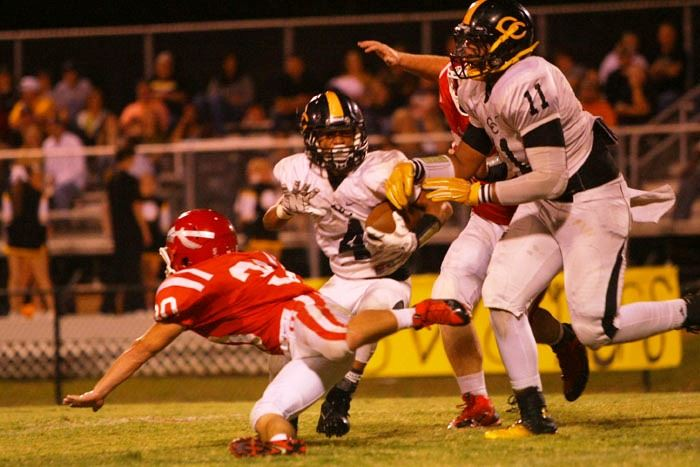 Cherokee County's Brendan Bray (4) looks to evade Ohatchee's diving Josh Sexton. In the cover photo, quarterback Taylor Eubanks looks towards an open receiver; he threw three second-half touchdown passes for the Indians. (Photos by Greg McWilliams)
