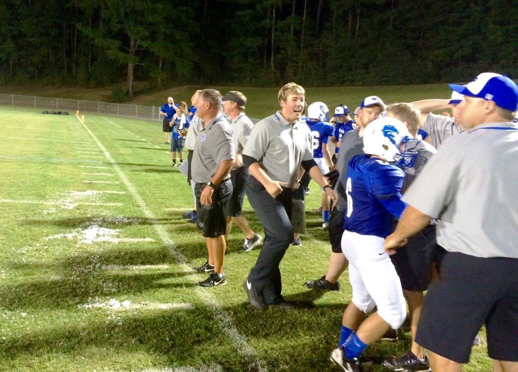 The remnants of his celebratory encounter with the water cooler lay before White Plains football coach Larry Strain in the closing minutes of Friday night's victory. In the cover photo, the players chase down Strain to take part in the tradition.