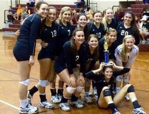 The Donoho volleyball team poses with the trophy after winning the Silver Bracket of its tournament Saturday. In the cover photo, Camille Fink (7) and Madison Gaines strike a pose at the net.