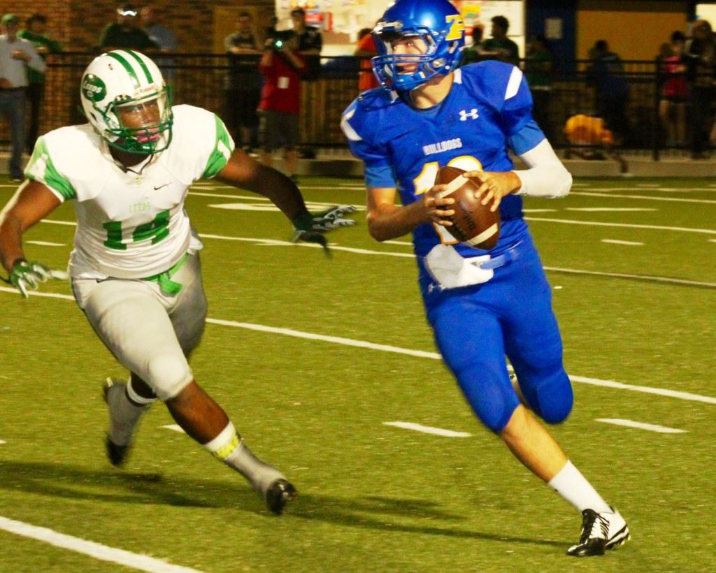 Piedmont quarterback Tyler Lusk (R) rolls out to avoid the pressure of Leeds' Javier Burrows. In the cover photo, Leeds' quarterback Tadarryl Marshall accounted for four Green Wave touchdowns Thursday night. (Photos Special to East Alabama Sports Today)
