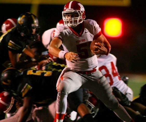 Munford quarterback Brett Haynie looks for running room against Lincoln last week. In the cover photo, the Lions get airborne to celebrate a big play.  (Photos by Greg McWilliams).