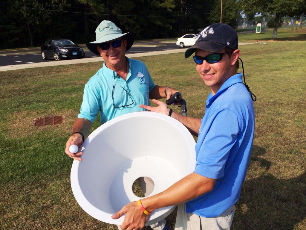 Anniston city golf director Kenny Szuch (L) and Jackson Johnson display the containers that will serve as holes for the introductory FootGolf course being set up adjacent to the soccer complex at McClellan.