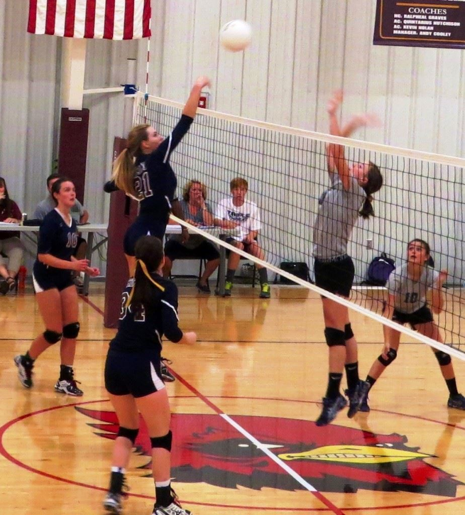 Sacred Heart's Olivia Simmons (21) goes high to get one of her five blocks in the Cardinals' sweep Thursday.