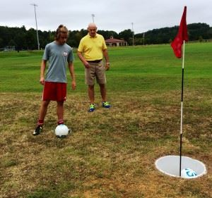 """Pete Eschrig (R) helps Oxford's Grant Biehunko line up a FootGolf """"putt"""" during Saturday's introduction. In the main photo, Eschrig pulls out a few birdies with FootGolfers (from left) Wilmer Alvarez, Ray Alvarado and Jose Alvarez."""