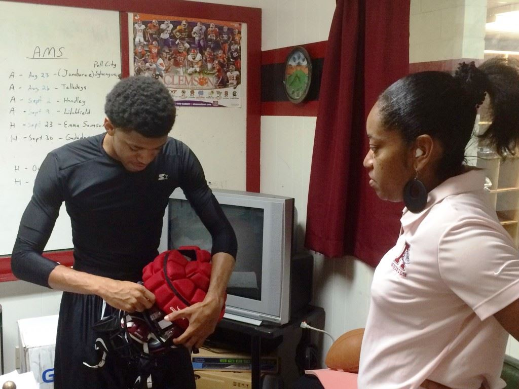 Anniston safety TyQuez Bullock adjusts the guardian cap on his helmet under the watchful eye of his mother Tosha.