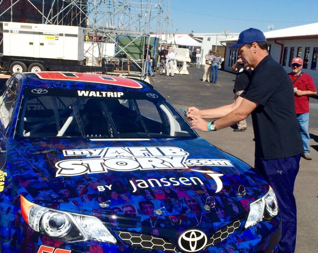 "Michael Waltrip takes pictures of people he recognizes among the 3,000 faces in the paint scheme of the Sprint Cup car he'll drive in Sunday's GEICO 500. Among those were his Dancing With The Stars partner Emma Slater and a couple Dale Earnhardt fans. During the walk-around he kept asking, 'Where's Alfonso?"" a reference to DWTS competitor Alfonso Ribiero."