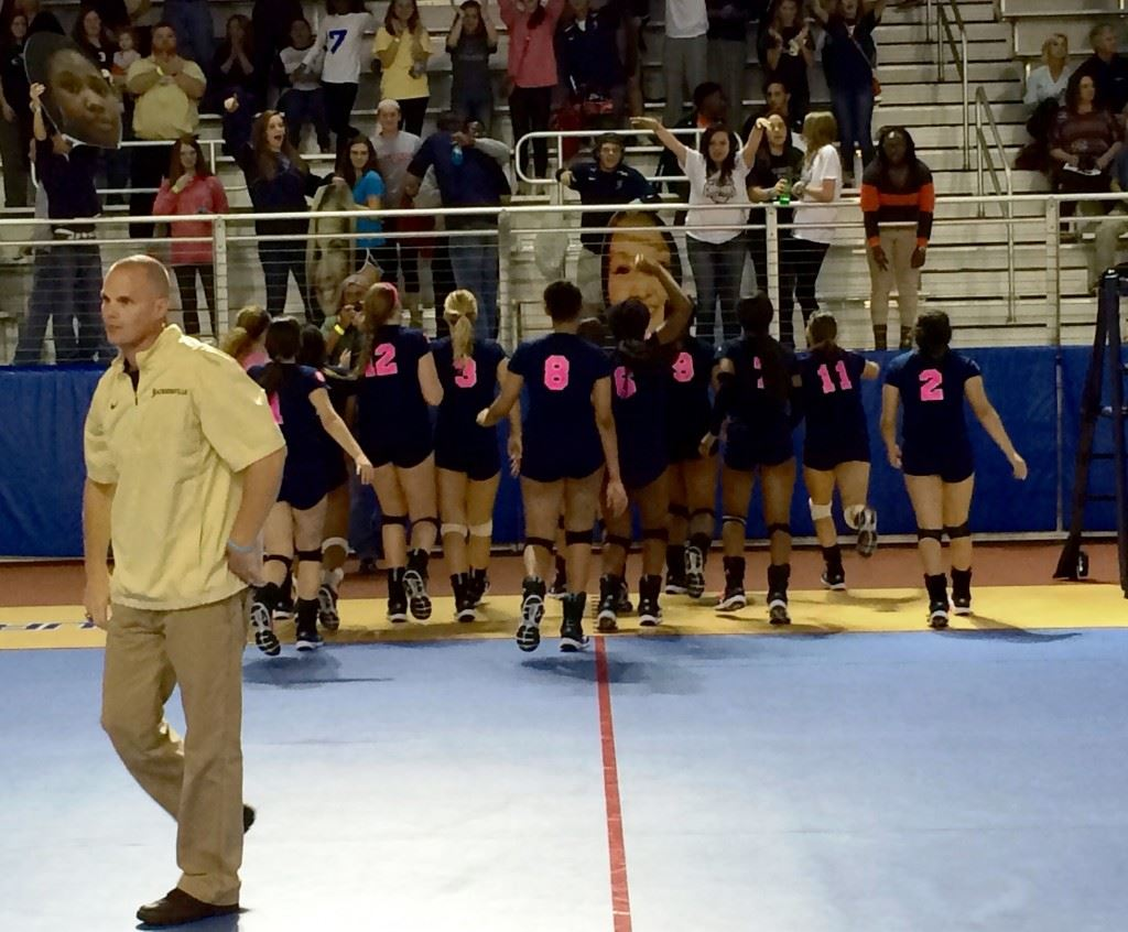 Jacksonville coach David Clark returns to the bench as his players rush to salute their fans after advancing to the Class 4A state championship match.
