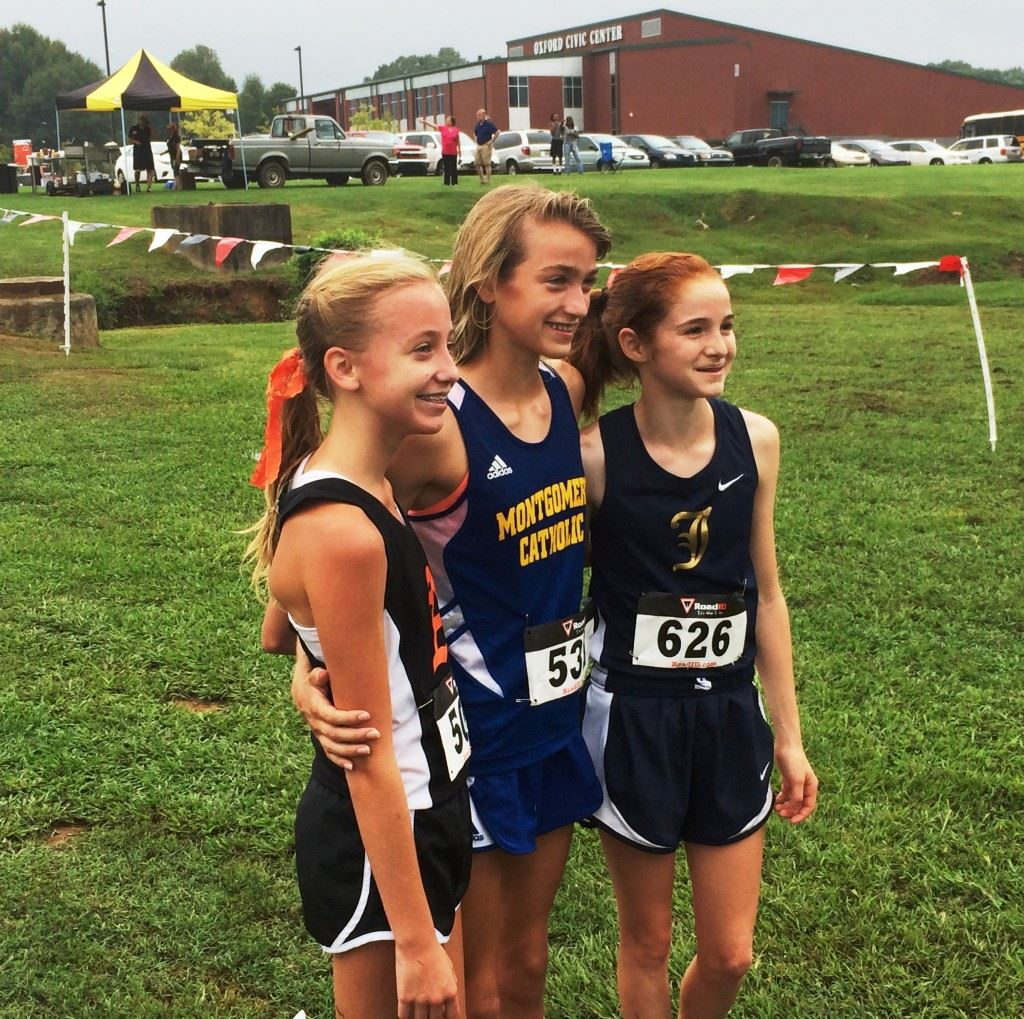 Alexandria's Abby Nunnelly (L) and Jacksonville's Rebecca Hearn (R) flank Catholic-Montgomery's Amaris Tyynismaa after running earlier this year at Oxford Lake. All three are expected to finish high in their respective state championship races Saturday in Moulton. Hearn and Tyynismaa are in the same race (4A).