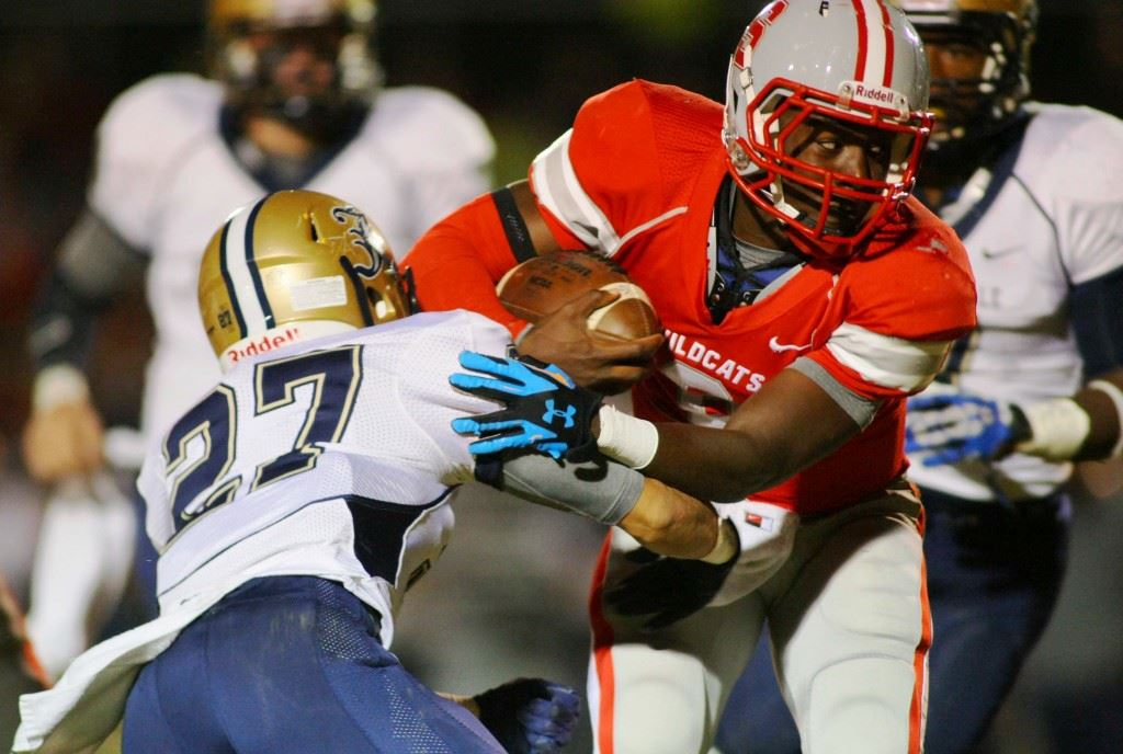 """Saks quarterback Devin Harris (6), who backfield mate Calvin Figueroa called """"a running back at heart,"""" tries to slip past Jacksonville's Nick Gangwer. (Photos by Greg McWilliams)"""