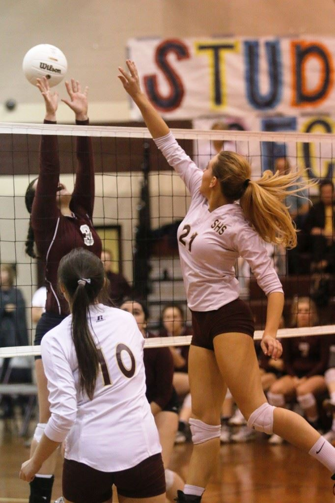 Sacred Heart's Olivia Simmons (21) sends one of her 20 block attempts over the outstretched hands of Donoho's Hannah Christian (3) during Monday's area title match. (Photo courtesy of Kristen Stringer/Krisp Pics Photography)
