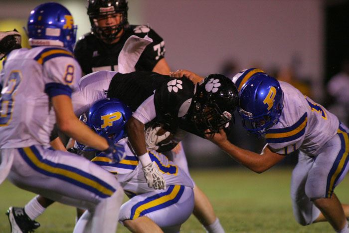 The Piedmont defense swarms around a Wellborn ball carrier Friday night. In the cover photo, Wellborn coach Jeff Smith reacts to the prospects of an upset slipping away. (Photos by Greg McWilliams)