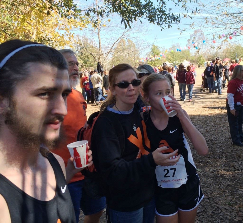 Alexandria's Abby Nunnelly (27) watches the finish of the Class 5A girls race unfold with her mother Amy. On the cover, Nunnelly gets support from a race aide after finishing second.