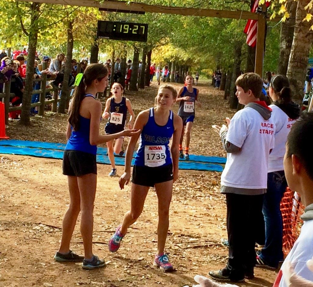 Jacksonville's Rebecca Hearn (825) beats West Limestone's Cassidy Winter to the line for fifth place in the Class 4A girls race. Then (below) she gives big brother Braden a big hug for winning his dare.