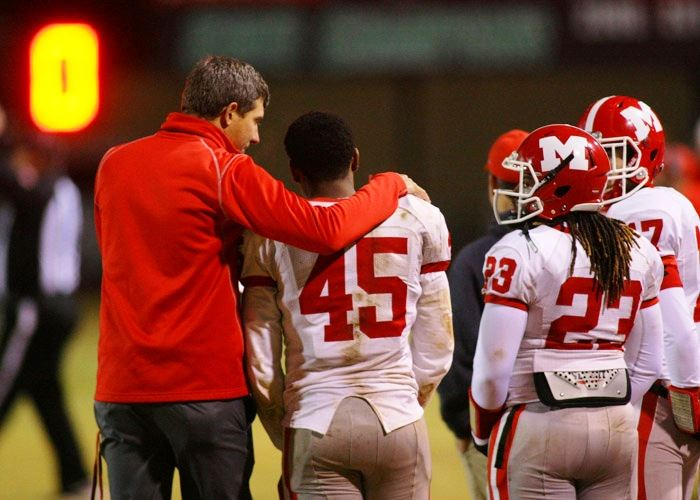 Munford coach Will Wagnon consoles senior linebacker Takeo Hall late in the Lions' playoff loss to Leeds. In the lower pictures, Leeds' Tre Nation (7) runs past Austin Campbell and Trey Roberson (79) tries to clear a path for Calvin Smith. (Photos by Greg McWilliams)