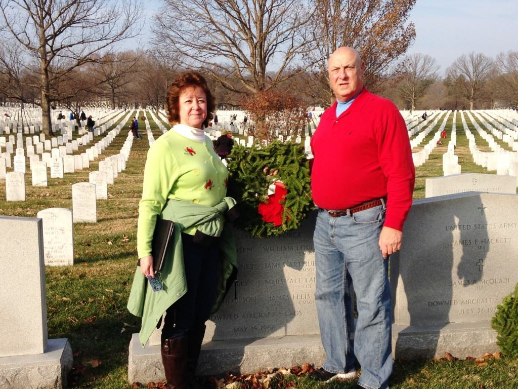 Pleasant Valley football coach Jeff Davis and his wife Dotty prepare to lay a wreath at the grave of the uncle of one of his assistant coaches interred at Arlington National Cemetery. On the cover, Davis kneels beside the headstone marking the grave of James Arthur Preston, the uncle of Raiders assistant coach Ronnie Preston. Below, children pause after laying a wreath at a gravesite. (Photos courtesy of Jeff Davis)
