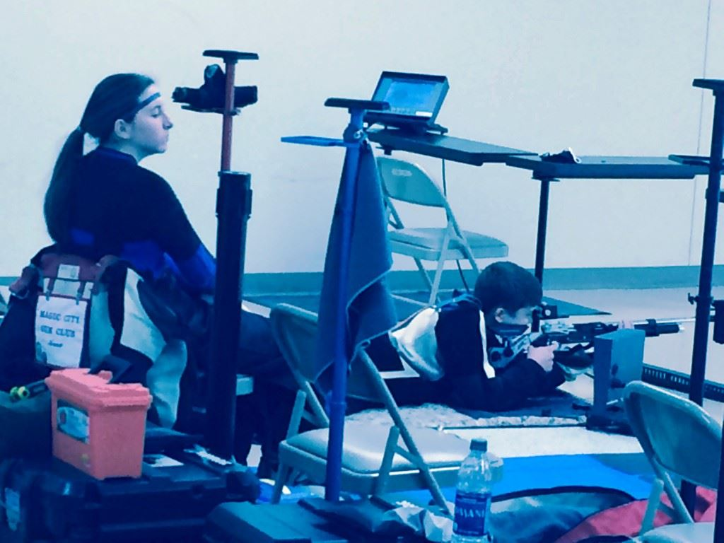 Anna Scheer (L) rests while Ryan McAndrews completes his prone relay at the CMP Alabama State Air Rifle Championships. Below, Alexis Poke secures her gun after finishing a winning Sporter program.