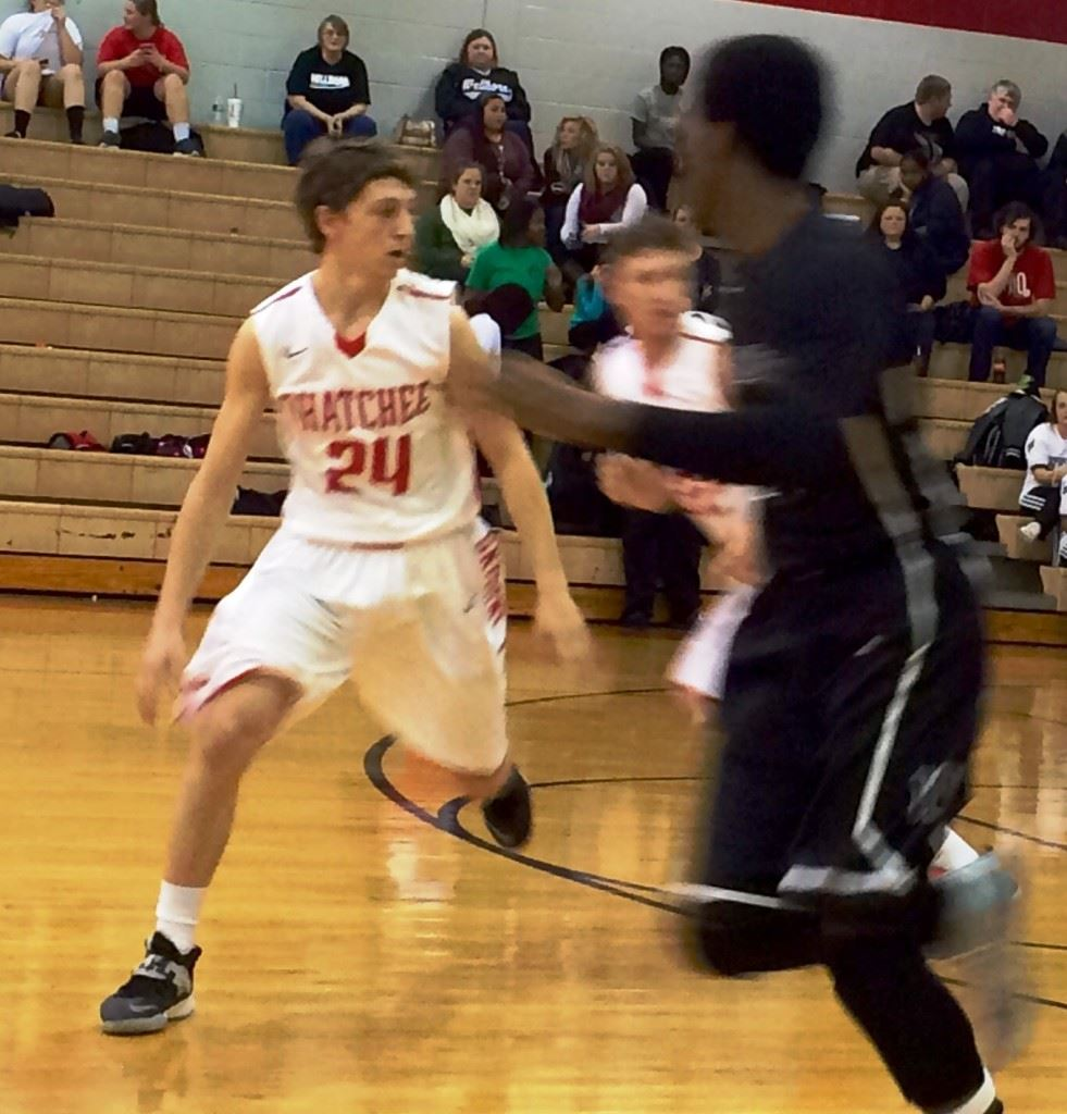 Ohatchee's Austin Tucker (24) considers doubling back for a loose ball; his two free throws with 2.4 seconds left won the game. On the cover, Wellborn's Corri Tignor (4) goes high for a potential rebound.