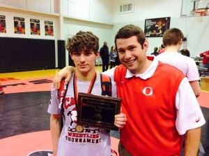 Ohatchee's Payton Entrekin (L), with coach Matt Sweatman, was voted most valuable wrestler of the tournament. On the cover, Oxford coaches Matt Tanner (L) and Brandon Jerome intently watch their wrestlers.