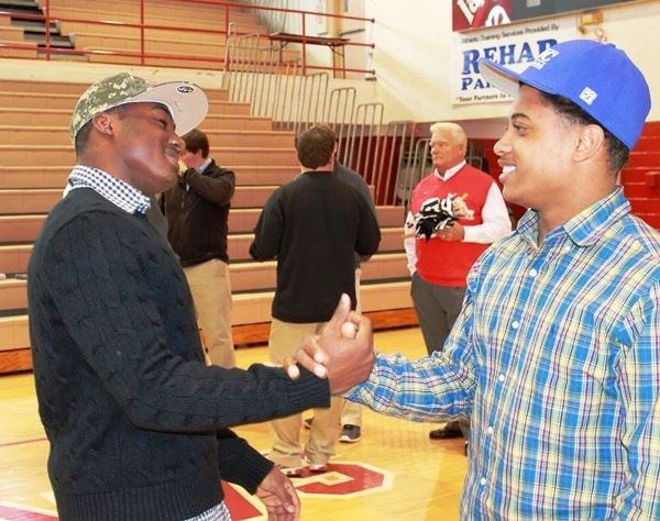 Saks quarterback Devin Harris (L) and Wellborn running back Kevin Mixon share a moment at Harris' signing ceremony Wednesday. The cousins made an appearance at each other's ceremony. (Photo by Bridget Merriman)