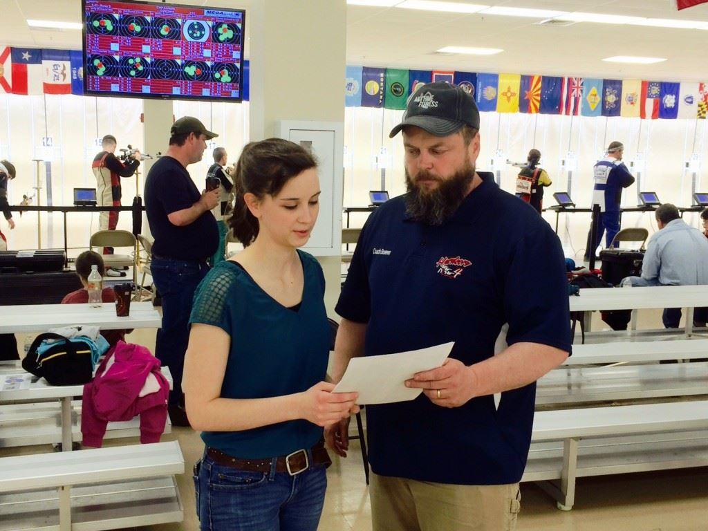 Rachel Kimbell reviews her results with coach Al Bowen after winning the air rifle competition at the Dixie Challenge. On the cover, Enterprise's Cori Horton shoots from the standing position.