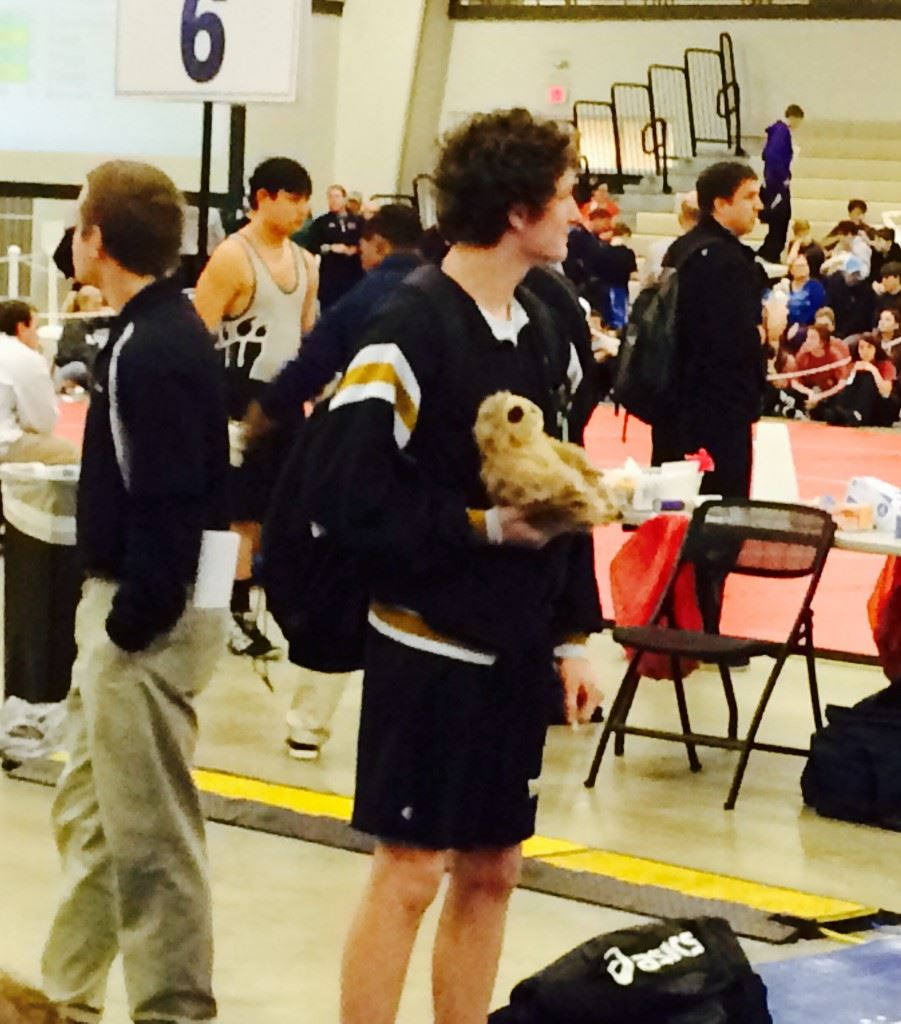 Oxford freshman Matt King watches the action on another mat while holding the Yellow Jackets' 'game sloth.' The Jackets have used the furry creature as a rallying point this season. (Photo by Al Muskewitz)