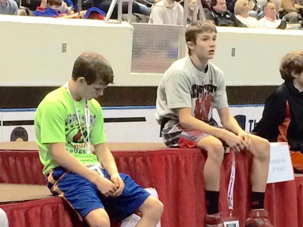 Weaver's Nick Souder (R) and Ohatchee's Jimmy Wilson await the awards ceremony after their 1A-5A 106 title bout. On the cover, Souder and Wilson lock up early in their match.