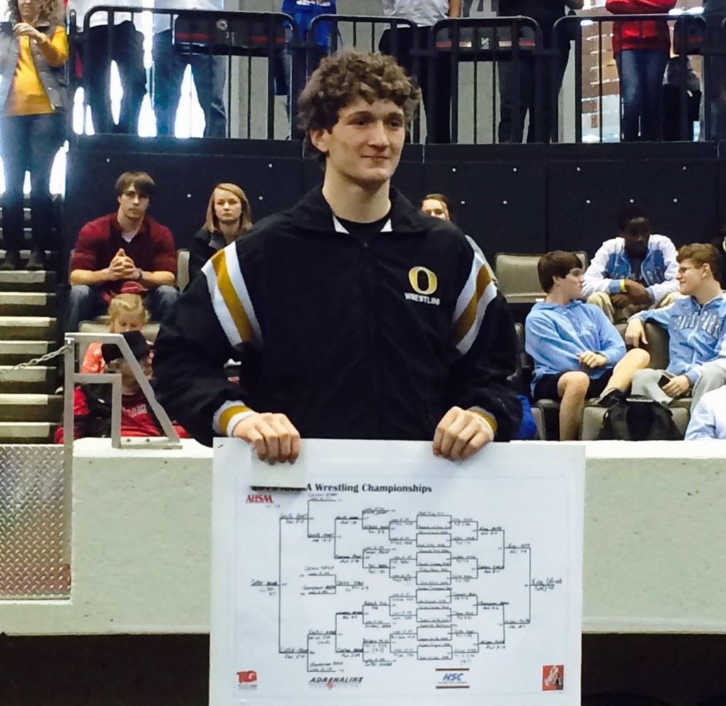 Oxford's Matt King stands on the podium with a copy of the 6A 138-pound weight class he dominating to win the state championship.