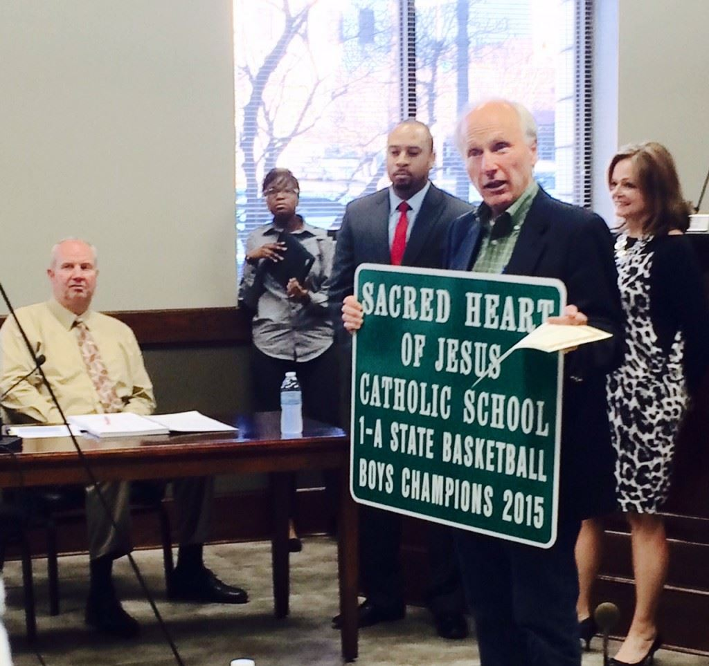 Anniston mayor Vaughn Stewart holds the road sign and a copy of the city resolution recognizing Sacred Heart's Class 1A boys basketball state championship.