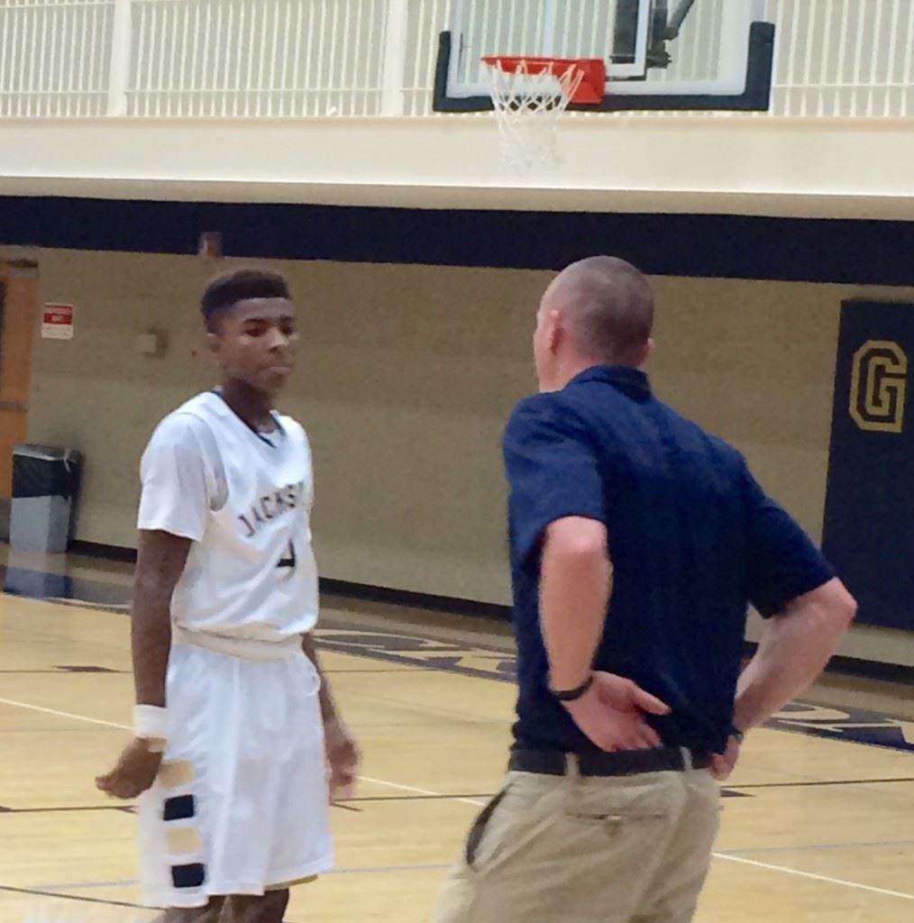 Jacksonville scorer Cam Horton gets some instruction from Golden Eagles coach Ryan Chambless.