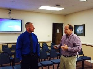 New White Plains football coach Chris White (L) talks with Calhoun County school board member Phil Murphy after being approved by the board Thursday night.