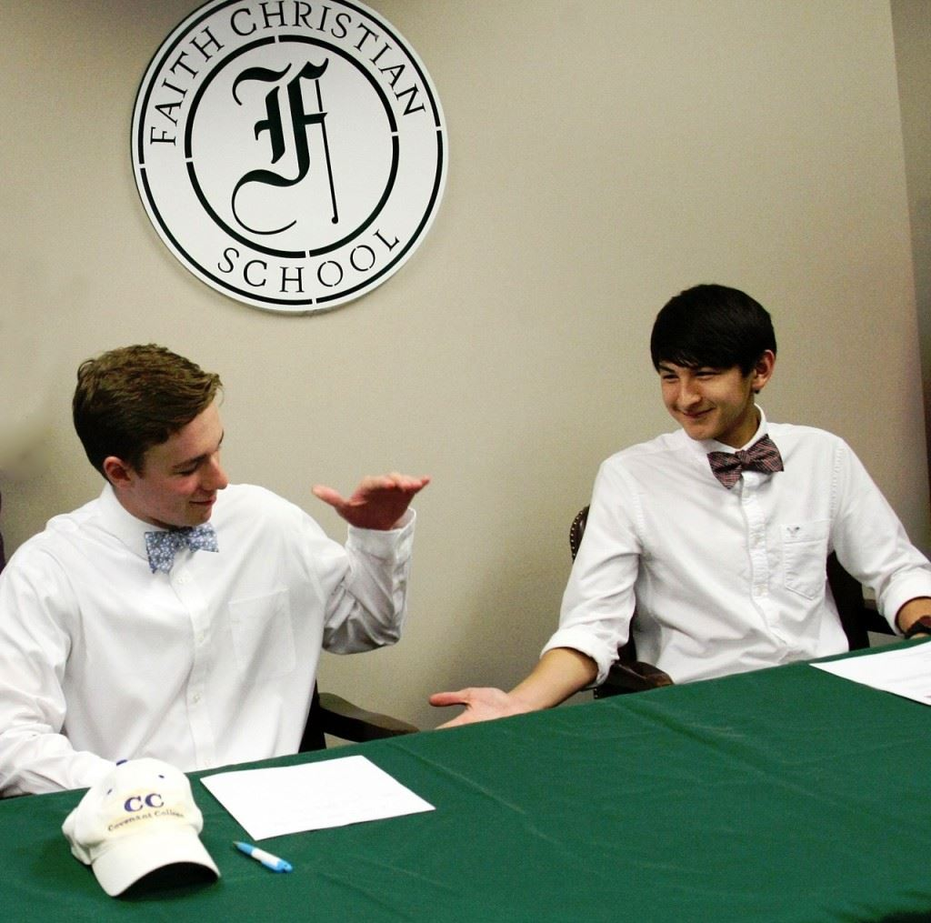 Faith Christian seniors Josiah McDaniel (L) and Tyler Johnson congratulate each other after their college signing ceremony Wednesday. (Photo by Carey Jenkins)