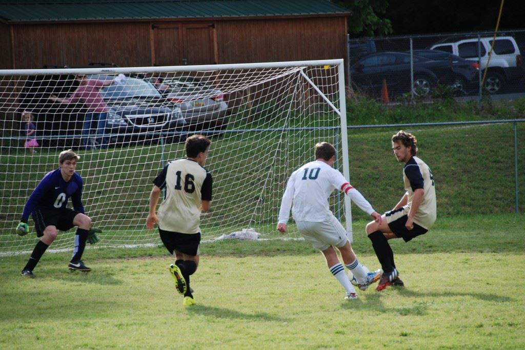 Faith Christian's Josiah McDaniel (10) splits two Altamont defenders and freezes the keeper before scoring the game's second goal. (Photo by Tony Bedford)