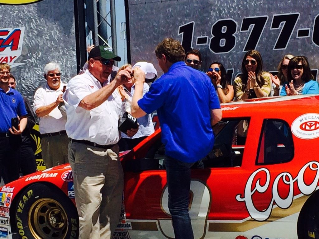 Talladega Superspeedway chairman Grant Lynch (L) greets Bill Elliott in Victory Lane after the NASCAR Hall of Famer recreated his famous 1985 comeback in a four-lap run in that same car Wednesday. On the cover, Lynch, Elliott and Eli Gold share memories of that race.