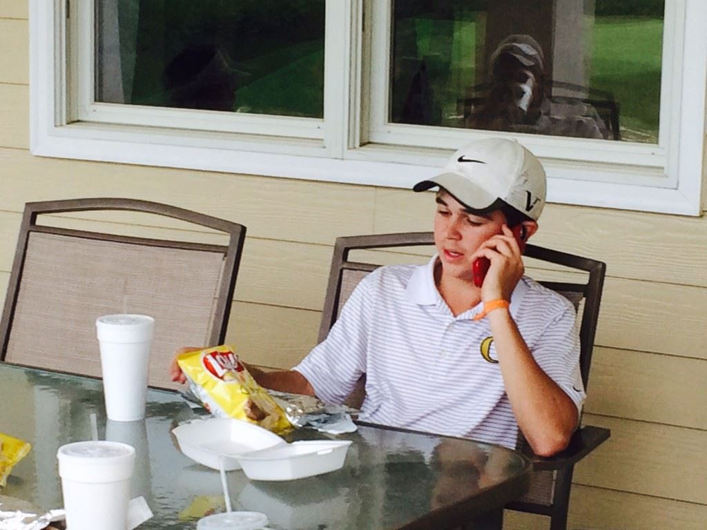 Oxford's Tyler Putnam takes in some lunch and a phone call after finishing second to help the Jackets qualify for the Class 6A substate tournament.