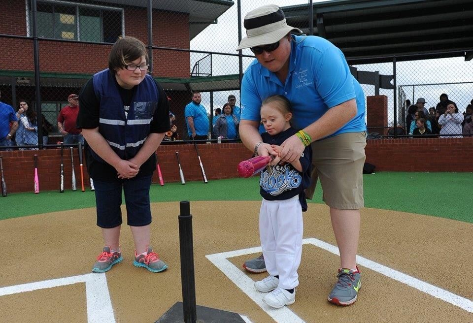 """Batter up! A League of Our Own player gets an assistant from a """"buddy"""" during the facility's opening weekend. (Photo by Joey D'Anna)"""