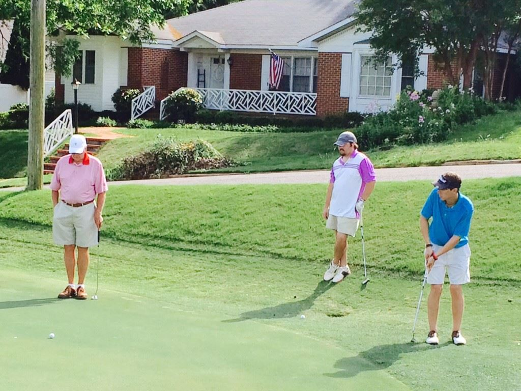 Jackson Johnson (R) rolls a putt from the fringe on the 16th green Saturday. Waiting their turn to putt are Anniston Country Club's Bob Kennamer (L) and Johnson's Cane Creek teammate Janson Wilborn.