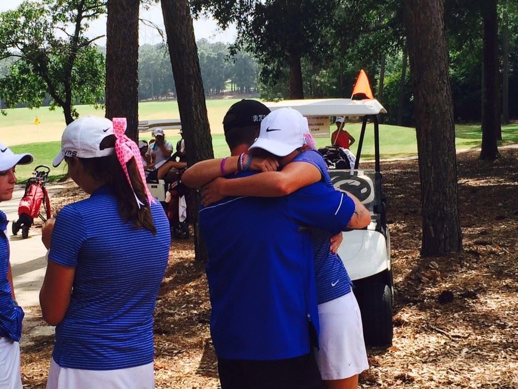 White Plains senior Raegan Thompson gives a big hug to assistant coach Brock Harrell after finishing her round in the state golf championship Tuesday.