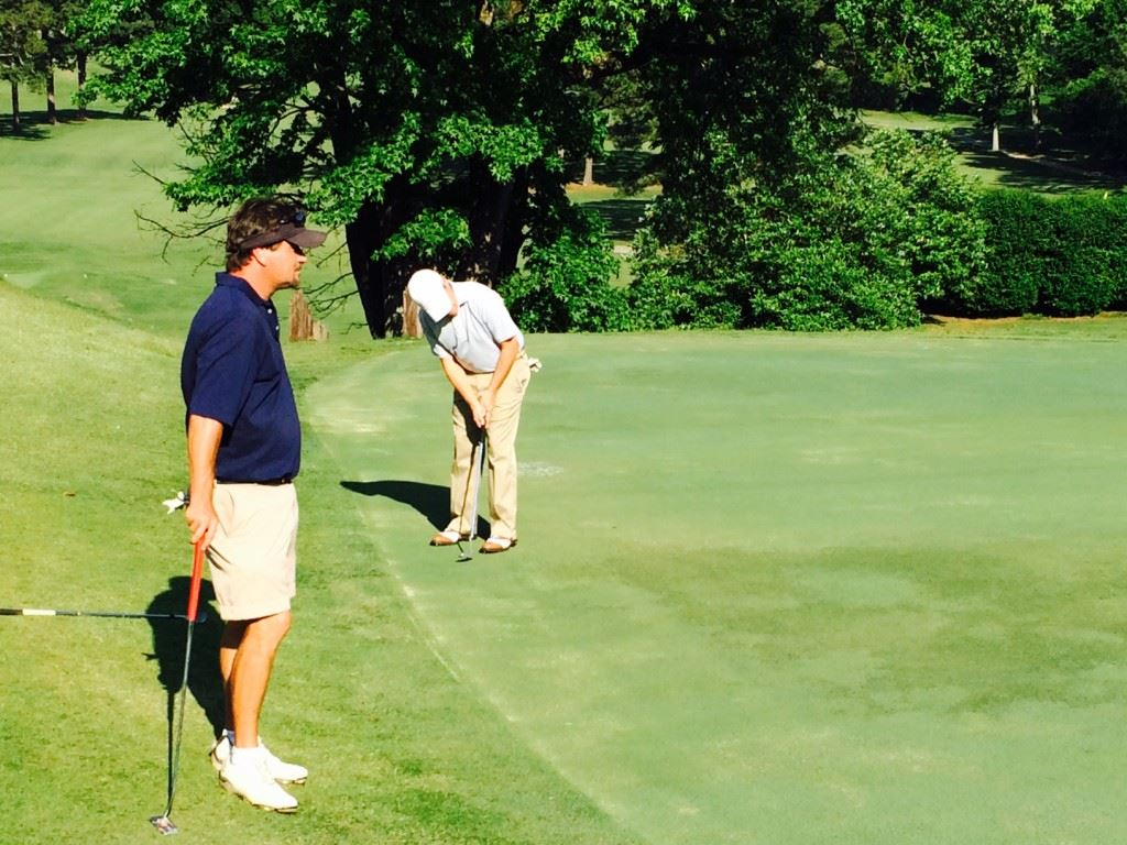 Brian Woodfin (L) stands by as partner Jake Spott rolls a birdie putt on the 16th green during Saturday's EA Sports Today Challenge Cup matches at Anniston Country Club.