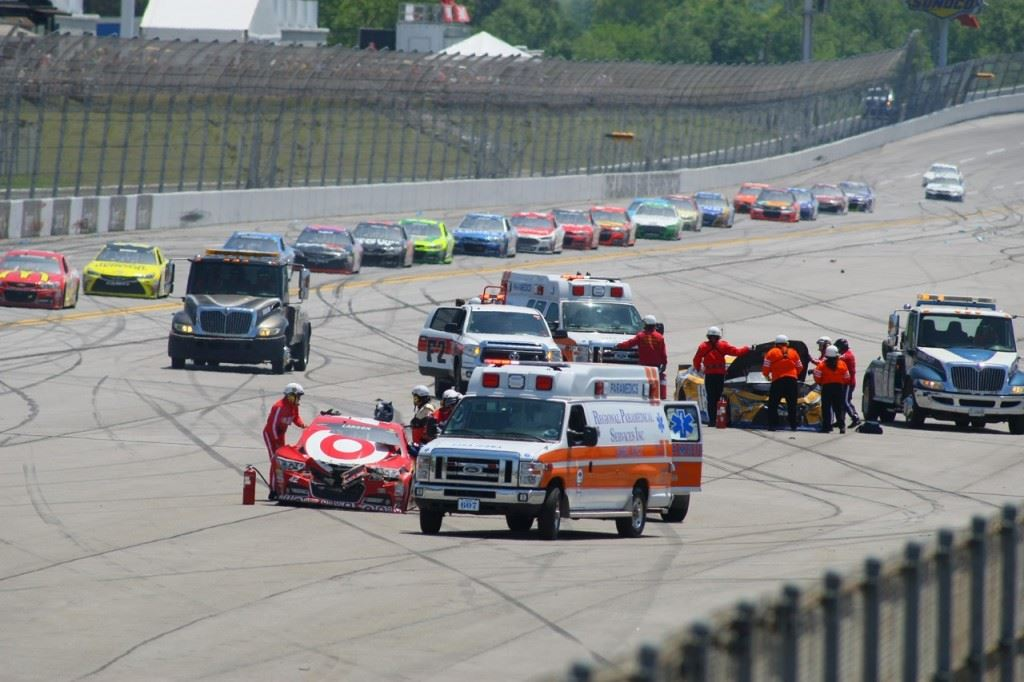 Emergency crews attend to crumpled cars while the race is red-flagged on Lap 47. On the cover, cars scatter during the biggest incident of the race.