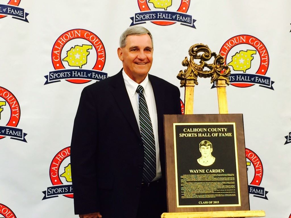 Wayne Carden stands with his plaque recognizing his induction into the Calhoun County Sports Hall of Fame. On the cover, inductees (from left) Howard Miller; Randy Cox, the son of Paul Cox; Carden; Henry O'Steen; Don Salls and Jerry Weems.
