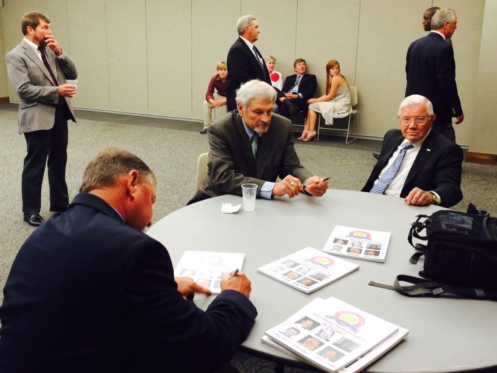 Calhoun County Sports Hall of Fame inductees (from left) Jerry Weems, Henry O'Steen and Don Salls autograph programs before the start of the formal enshrinement ceremonies.