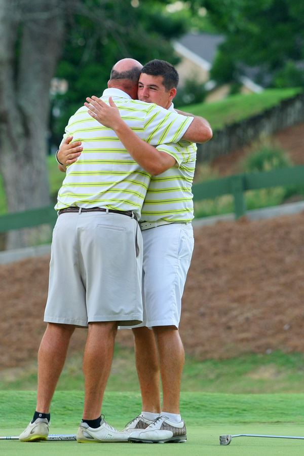 Ott Chandler (L) embraces son Dalton on the 18th green after they secured victory in the 37th annual Sunny King Charity Classic. (Photo by Greg McWilliams)