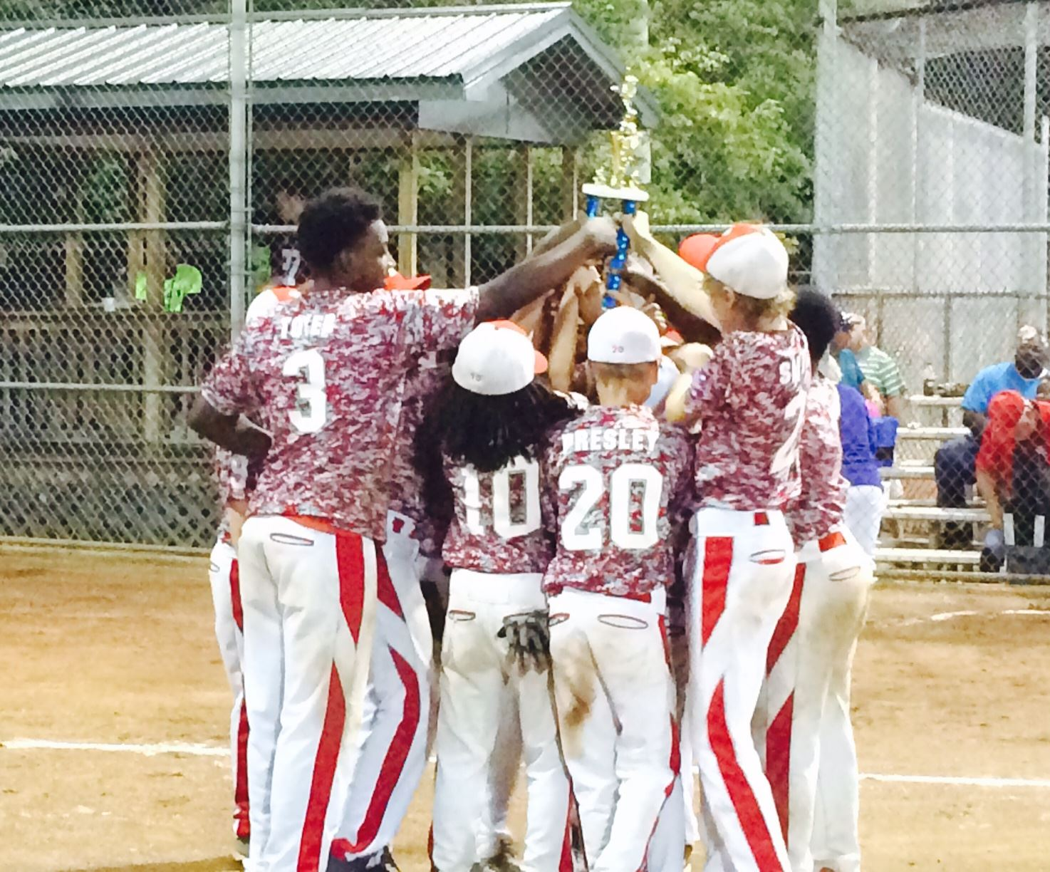 Pitchers Ontarius Toyer (3) and Cody Smith (2) join Munford teammates in raising the trophy after winning the District 2 Dixie Youth O-Zone title Monday night.