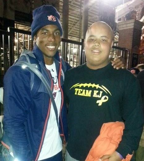 Oxford sophomore K.J. Lynch (R) spends a few minutes with Auburn and former Oxford back Roc Thomas on The Plains.