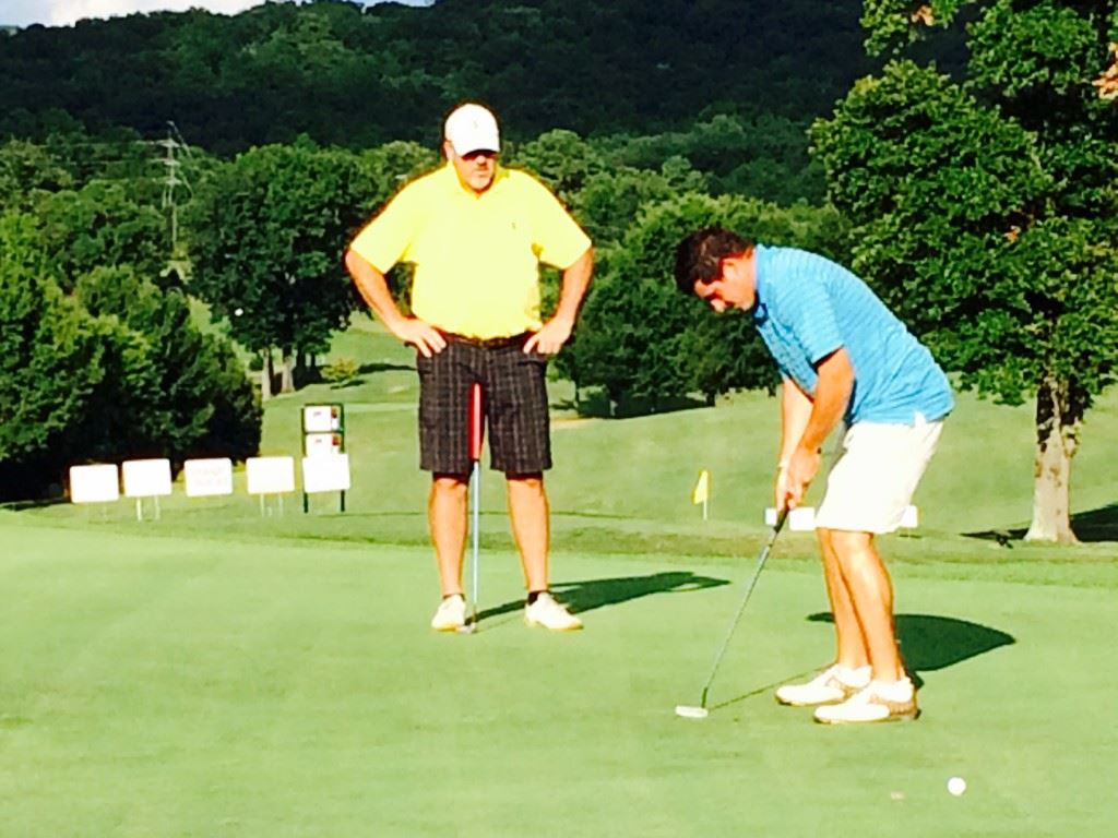 Dalton Chandler (R), under the watchful eye of his father Ott, sinks a 15-foot birdie putt on 18 that clinched the Buddy Moore Charity Classic.
